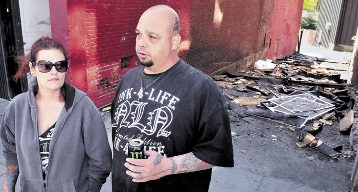 Mona and Bill Juliano, owners of Ink-4-Life tattoo parlor, speak Monday outside an alley littered with debris from the Waterville apartment building fire that destroyed their business and left tenants homeless on Friday. The Julianos are planning to relocate across Main Street in the former Levine's building.