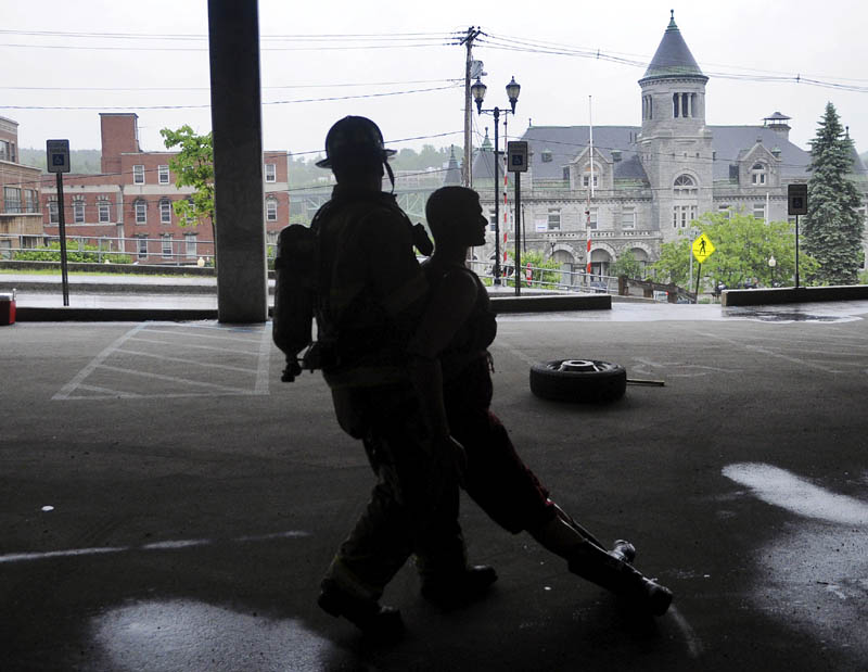 Brian Ackley, of Topsham, drags a life-size mannequin through a parking garage in Augusta on Tuesday during a physical agility test for prospective Augusta firefighters. A dozen candidates were tested on their dexterity, firefighting and emergency medical skills before being interviewed for potential openings, according to Deputy Fire Chief David Groder.