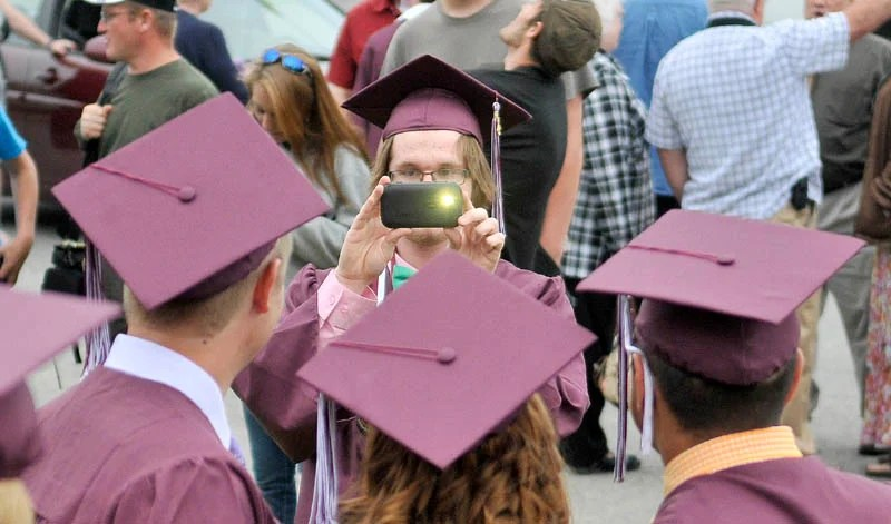 Jackson Pendleton, facing center, takes photos of friends before Nokomis High School's commencement ceremonies in Newport on Friday.