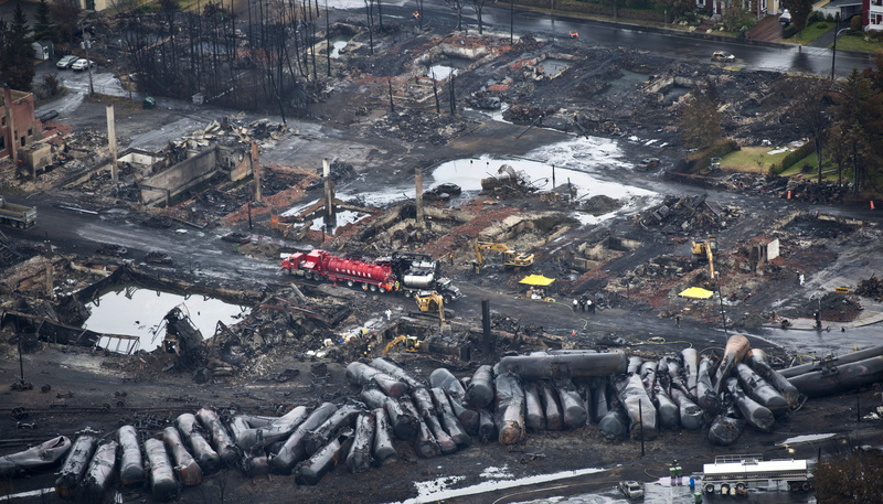 Workers comb through debris July 9, three days after a runaway train derailed, causing explosions, fire and destroying parts of Lac-Megantic, Quebec. Gov. Paul LePage will visit the stricken community to attend a memorial Mass for the victims.