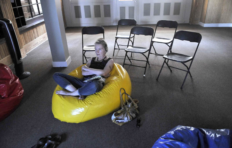 """Karen Young watches a MiffOnEdge presentation of Nam Jun Paik's """"Global Groove"""" from a bean bag chair at the old post office in downtown Waterville on Saturday."""