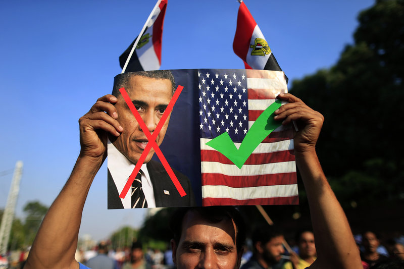 An opponent of Mohammed Morsi, Egypt's recently deposed president, holds up a picture showing U.S. President Obama and the U.S. flag at a rally in Cairo, Egypt, on Sunday.