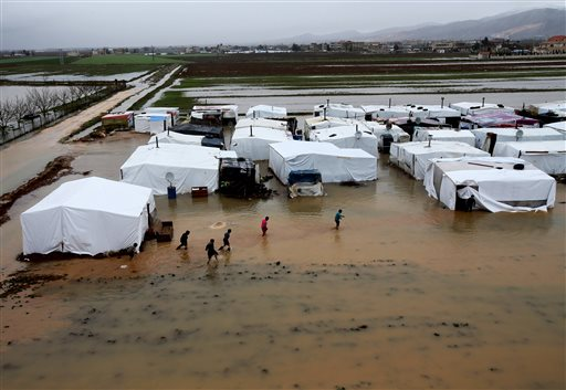In this Jan. 8, 2013, photo, Syrian refugees make their way in flooded water at a temporary refugee camp, in the eastern Lebanese town of Al-Faour near the border with Syria.