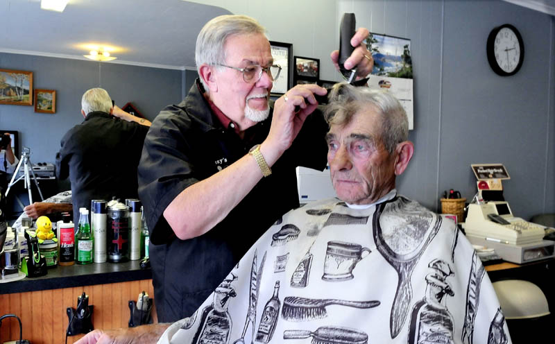 """Freeman """"Buzzy"""" Buzzell cuts the hair of customer Ron Frazier at his shop on Main Street in Madison recently. Buzzell said he has been a barber for nearly five decades and enjoys his customers and meeting new ones."""