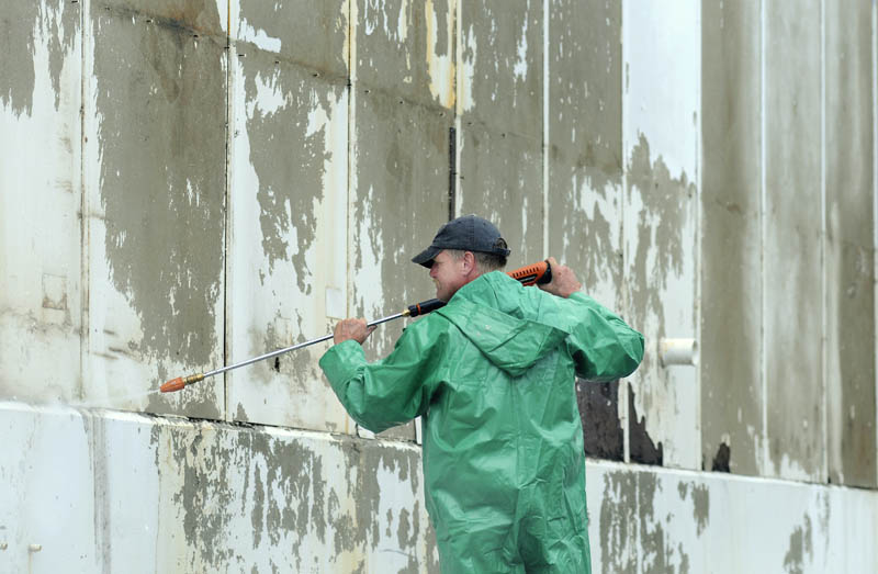Skeeter Arnold blasts paint Monday off the loading dock of a warehouse in South Gardiner. A crew from Tim Dennett Property Management was taking advantage of wet conditions to pressure wash the paint off the building before applying new coats later in the week.
