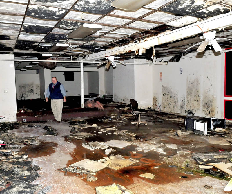 John Weeks walks through the damaged first floor of his Main Street building in Waterville that was destroyed by fire last May. Weeks says he plans to demolish the structure and may rebuild at the location.