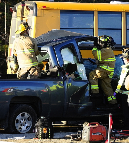 Emergency crews remove the roof: of a pickup truck as they work to free a driver at the scene of a crash involving an Augusta school bus Tuesday on Riverside Drive, just south of Stevens Road, in Augusta.