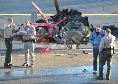 """Sheriff's deputies work near the wreckage of a Porsche that crashed into a light pole on Hercules Street near Kelly Johnson Parkway in Valencia, Calif., on Saturday. A publicist for actor Paul Walker says the star of the """"Fast & Furious"""" movie series died in the crash north of Los Angeles. He was 40."""