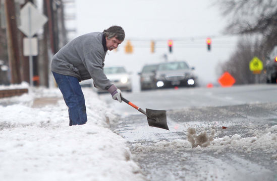 Jerry Lord clears snow from the shoulder of Lancaster Avenue in Wilmington, Del., on Monday. A storm that dumped heavy snow on the unsuspecting mid-Atlantic region left roads slippery and slushy in the Northeast for Monday's commute.