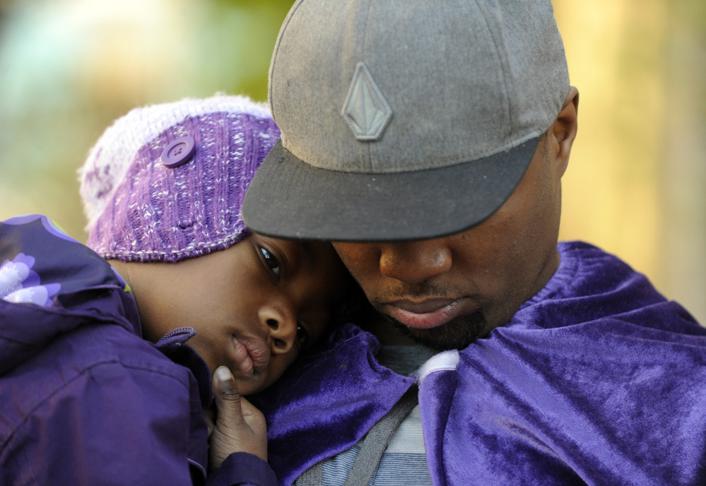 Quinton Reynolds, of Emeryville, Calif., holds his daughter Qniyah Reynolds, 4, outside of Children's Hospital Oakland in support of Jahi McMath in Oakland, Calif., on Monday.