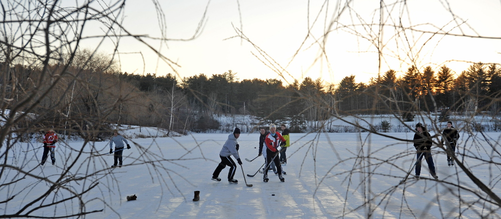POND PUCK: People play a pick-up game of hockey on Johnson Pond at Colby College in Waterville on Wednesday, Jan. 30, 2014.