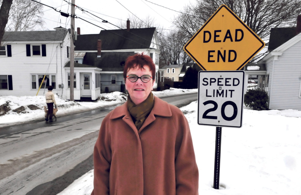 """ROOTS: Author Rhea Cote Robbins stands along Water Street in the South End section of Waterville. Her book """"'down the Plains'"""" is about growing up in a home nearby."""