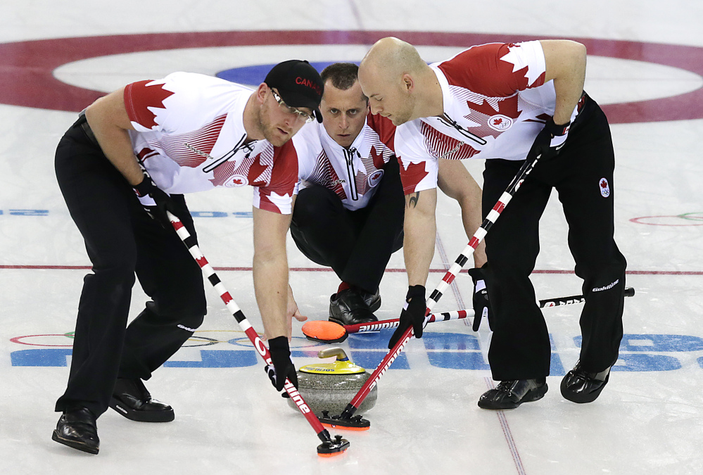 NOT SO FAST START: Canada's E.J. Harnden watches the rock as Ryan Harnden, left, and Ryan Fry sweep the ice against Germany Monday, Feb. 10, in Sochi, Russia. The Canadians' campaign has begun in underwhelming fashion after entering the men's curling competition as gold-medal favorites.