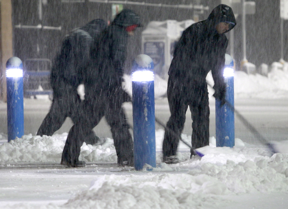 Workers clears snow from the sidewalk outside a business Saturday in the Boston suburb of Hudson, Mass.