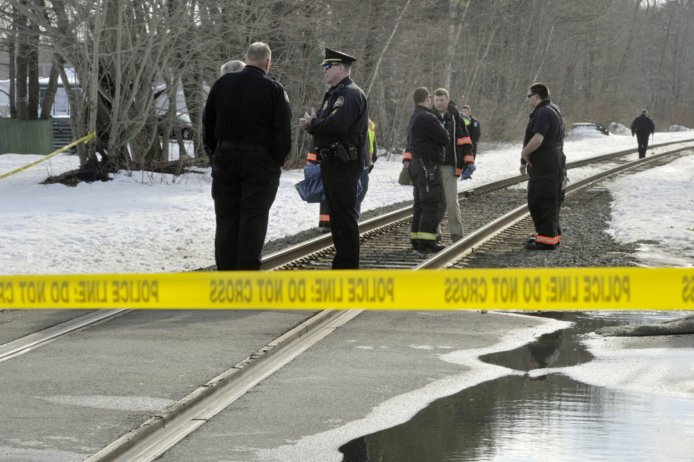 Old Orchard Beach police officers and firefighters and railroad police officers gather at the Union Avenue train crossing in Old Orchard Beach, where a man was struck and killed by a Downeaster on Tuesday afternoon in an apparent suicide.