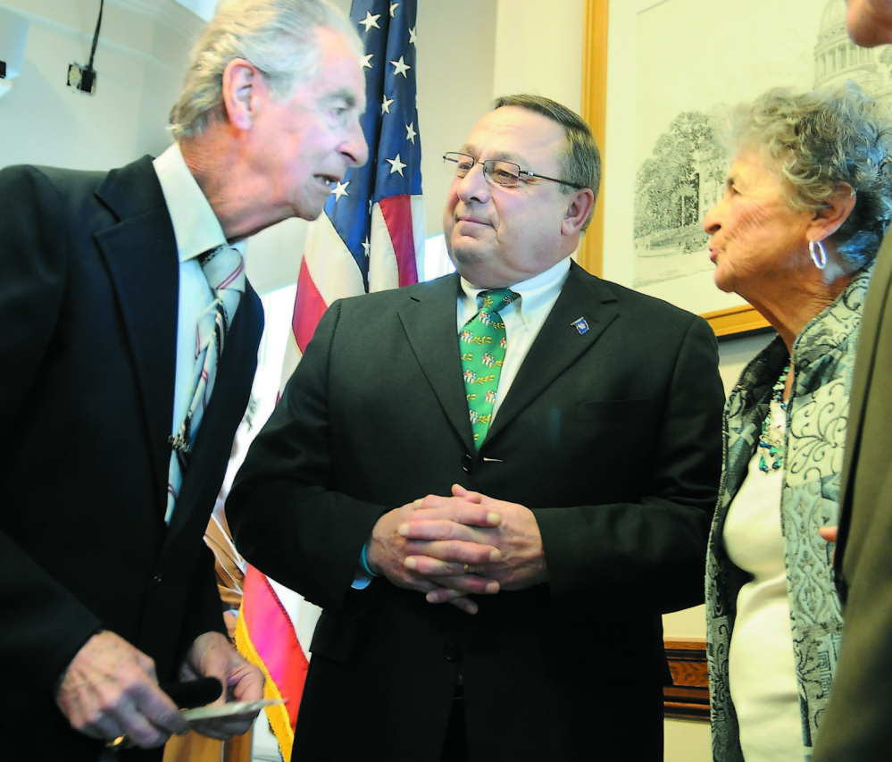 """HALL OF FAMER: In this 2012 file photo, Augusta resident Leo Pepin, left, and his sister, Madeline Patenaude, speak with Gov. Paul LePage after LePage signed a bill to designate the """"Dirigo March"""" as the official state march. Next week, Pepin will be inducted into the Franco-American Hall of Fame."""