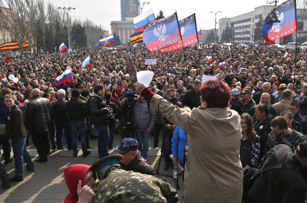 People shout slogans during a pro Russian rally at a central square in Donetsk, eastern Ukraine, on Saturday. Russian forces backed by helicopter gunships and armored vehicles Saturday took control of a village near the border with Crimea on the eve of a referendum on whether the region should seek annexation by Moscow, Ukrainian officials said.
