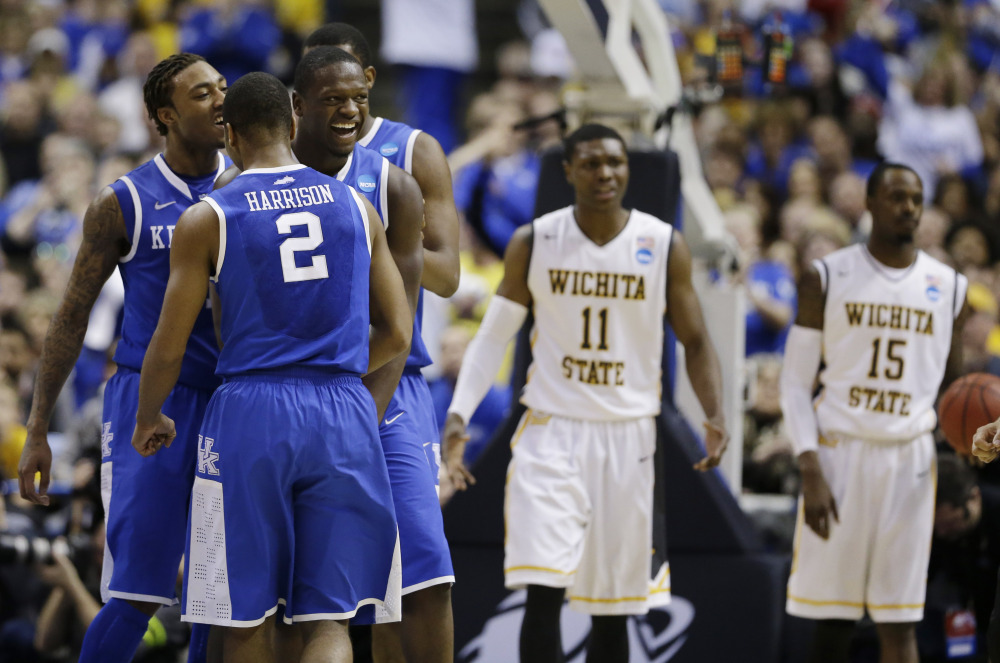 Kentucky players from left, guard/forward James Young (1), guard Aaron Harrison (2) and forward Julius Randle (30) celebrate against Wichita State during the second half of a third-round game of the NCAA college basketball tournament Sunday.