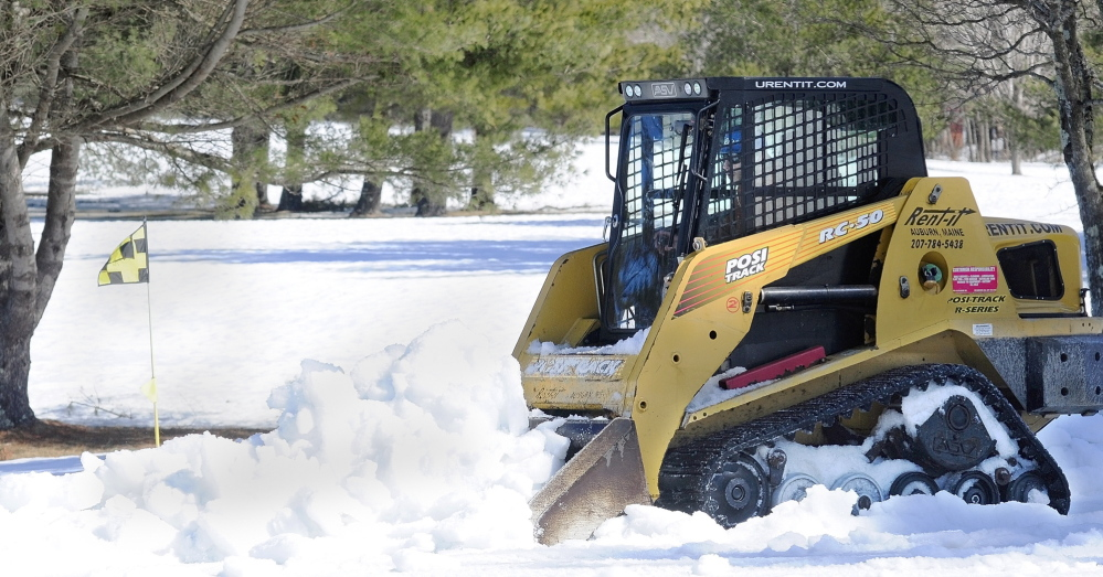 """Staff photo by Joe Phelan An Augusta Country Club employee drives a skid steer to plow snow off the 11th green on Tuesday in Manchester. """"Spring's around the corner,"""" said general manager Jason Hurd. They were getting the snow off the greens this week, but he didn't know when the course might be open for the year."""