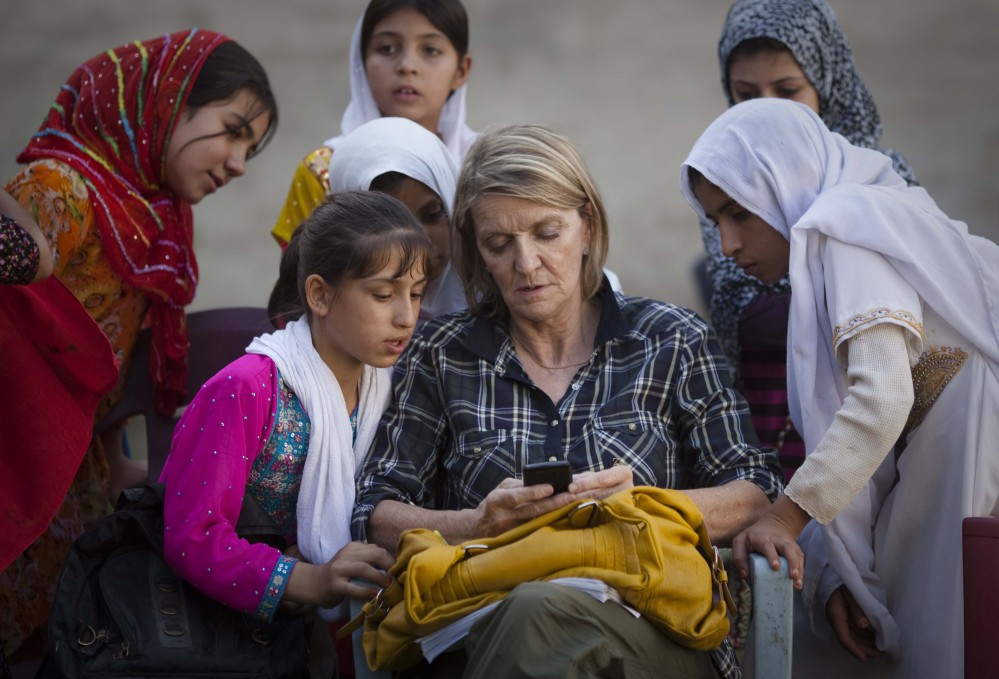 Regional Correspondent Kathy Gannon sits with girls at a school in Kandahar, Afghanistan, in this 2011 photo. Gannon, who was wounded Friday, is a Canadian journalist based in Islamabad for AP.