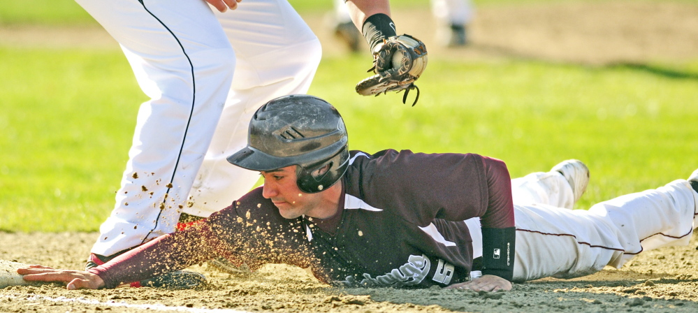 Monmouth Academy baserunner D.J. McHugh beats the tag from Hall-Dale first baseman Taylor Lockhart on pickoff play at first base during a game on Wednesday May 7, 2014 at Monmouth Academy. (Photo by Joe Phelan/Staff Photographer)