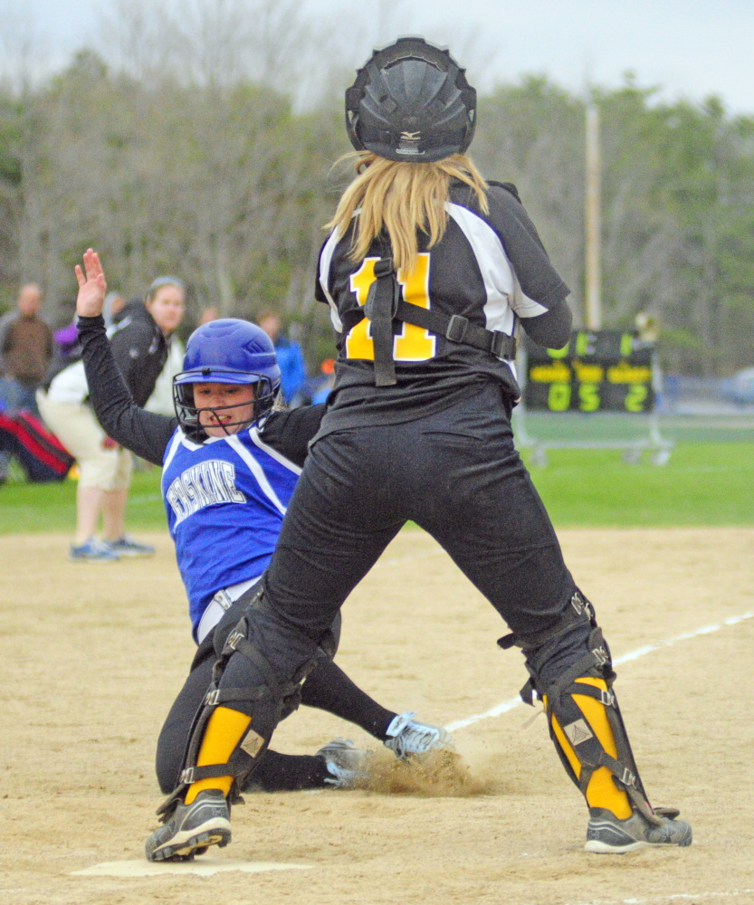 Erskine's Cassandra Ray slides but is out at the plate as Maranacook catcher Ashley Michaud waits to tag her during a game on Friday.