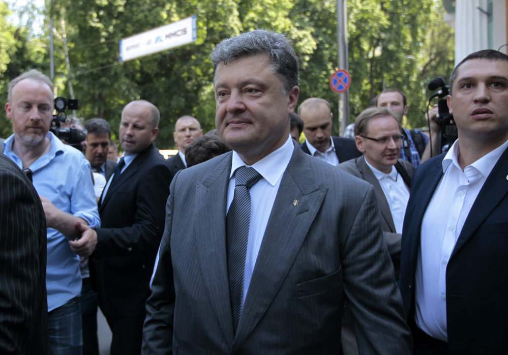 Ukrainian presidential candidate Petro Poroshenko speaks to press at a polling station after his vote during the presidential election in Kiev, Ukraine, on Sunday. An exit poll showed the billionaire candy-maker won Ukraine's presidential election outright Sunday in the first round – a vote that authorities hoped would unify the fractured nation.