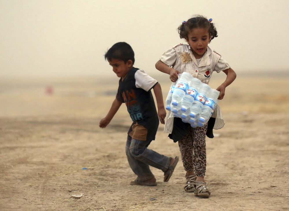 A girl who fled the violence in the Iraqi city of Mosul carries a case of water at a camp on the outskirts of Arbil in Iraq's Kurdistan region.