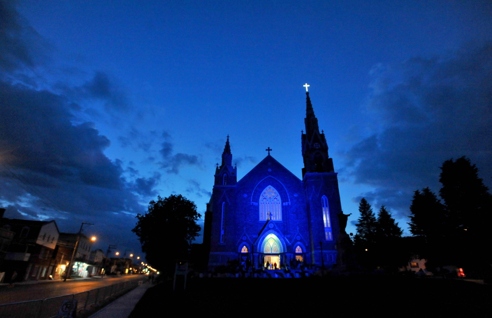 Ste-Agnes Catholic Church lights up in blue in the early hours of the morning during a vigil in Lac-Megantic, Quebec, on Sunday, July 6, 2014.
