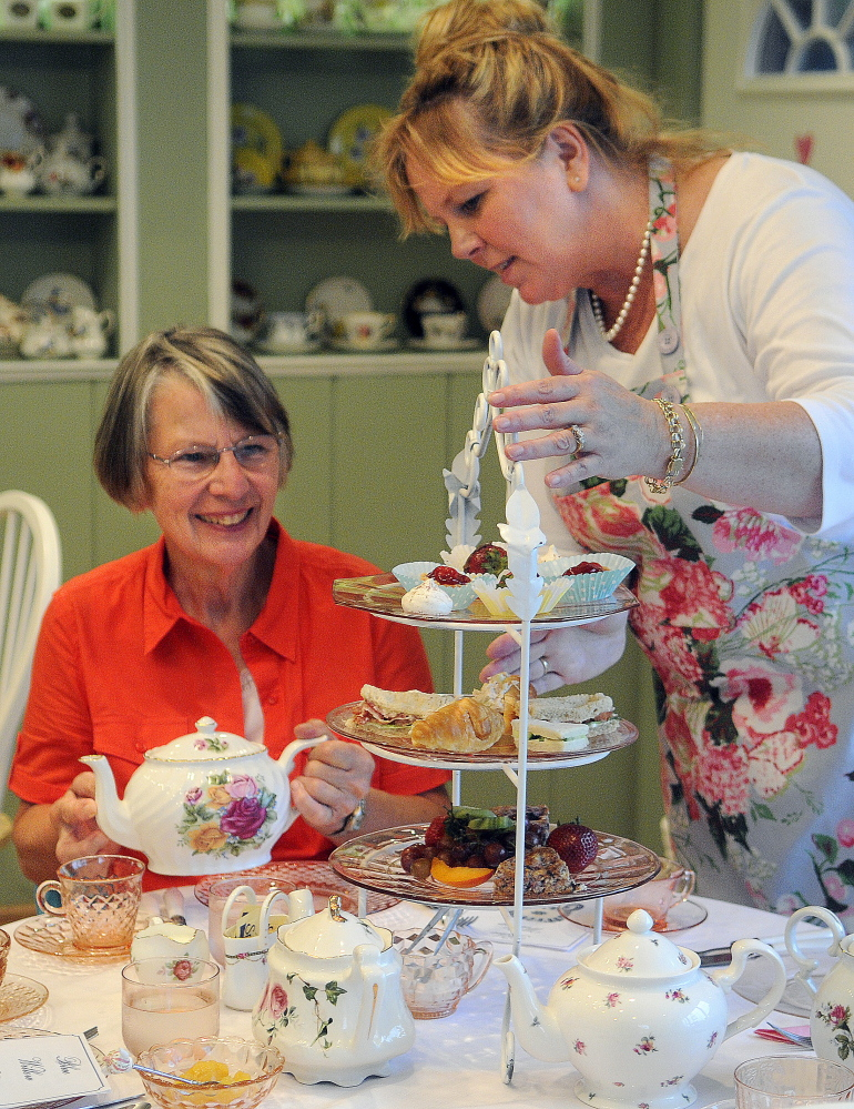 Patty Farrin, right, offers Diane Jerome sweets and sandwiches at the Blue Willow Tea Room in Randolph.