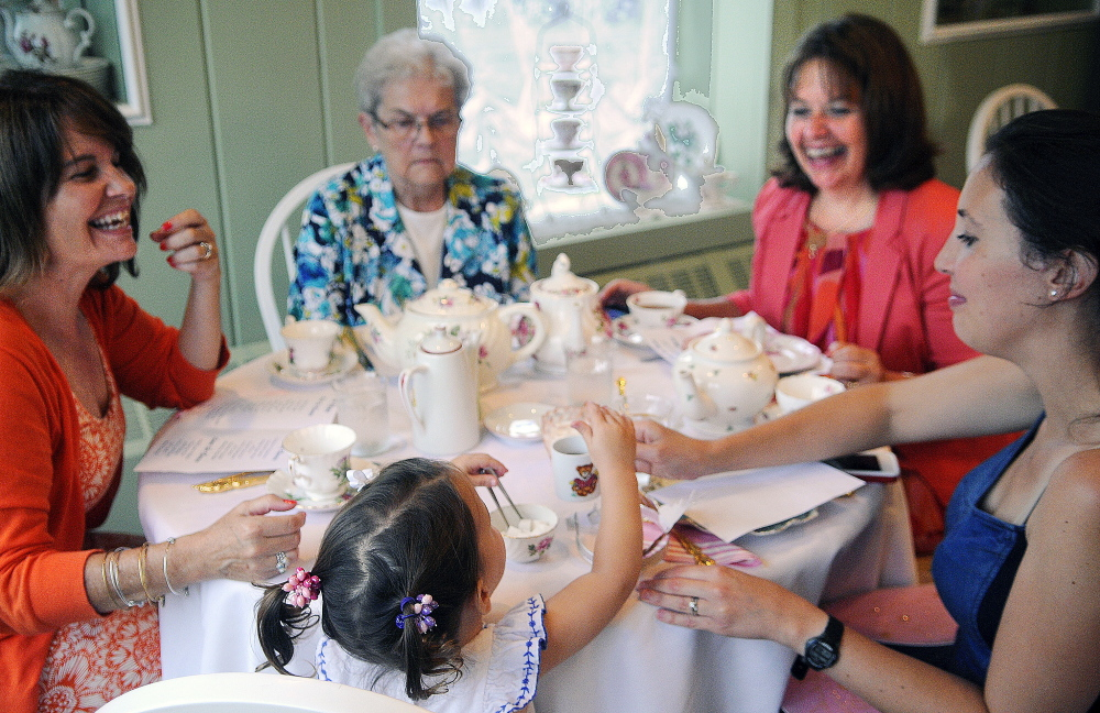 Caroline Merrill, 2, serves herself a sugar cube Monday while having tea with her mother, Jenny Merrill, right, aunts Anita Hopkins, left, and Heather Priest, second from right, and grandmother, May Coffin, top center, at the Blue Willow Tea Room in Randolph.