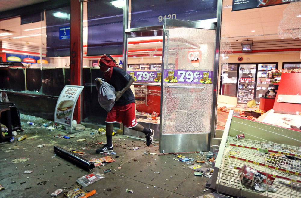 The Associated Press A man leaves a store on Sunday, in Ferguson, Mo.
