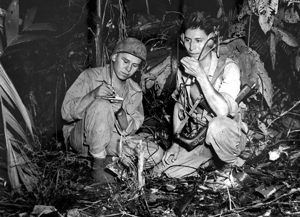 Marine Cpl. Henry Bake Jr. and Marine Pfc. George H. Kirk, Navajo Indians serving with a Marine signal unit, operate a portable radio set in a clearing they've hacked in the dense jungle close behind the front lines in December 1943 at Bougainville, in the territory of New Guinea.