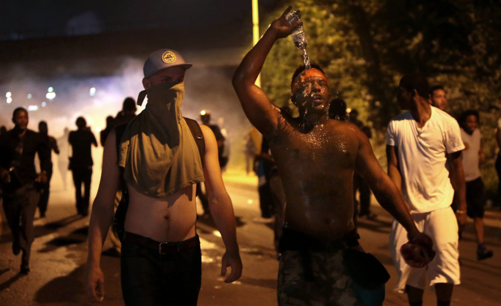 Protestors retreat from tear gas after marching toward police in Ferguson, Mo., Sunday.
