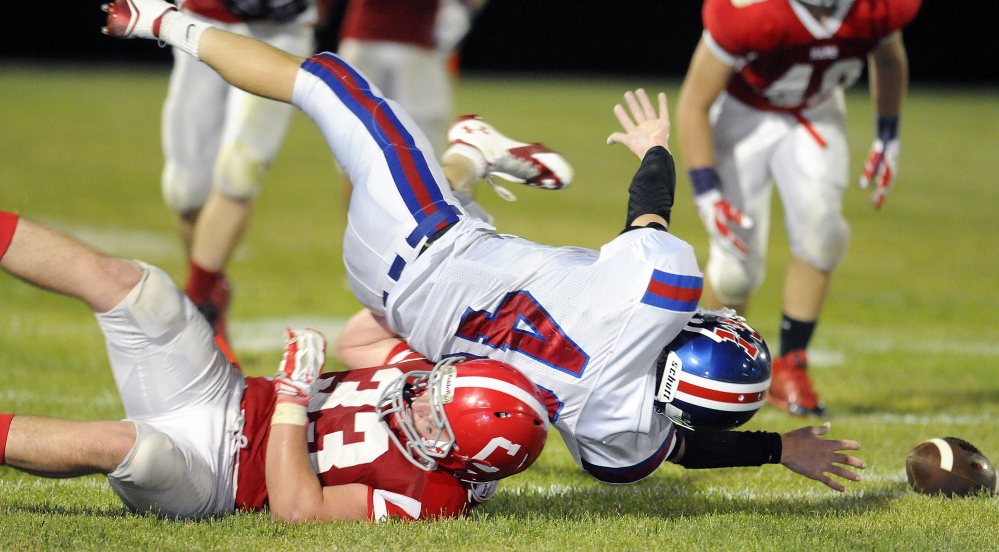 Messalonskee running back Caleb Chavarie is hauled down by Cony linebacker Reid Shostak during a Pine Tree Conference Class B game Friday night.
