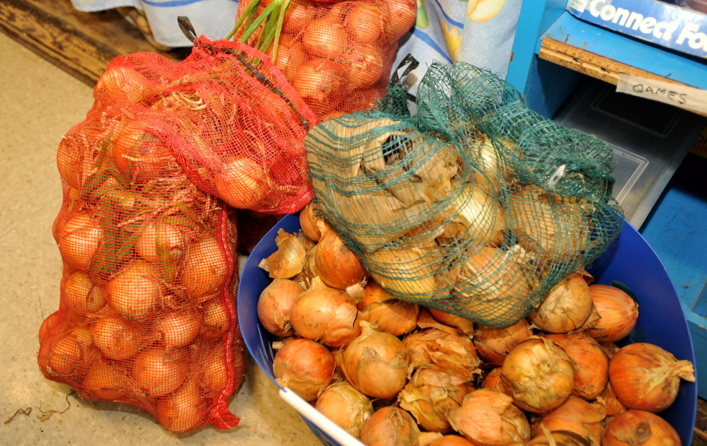 Sacks of donated onions wait for distribution at Albert S. Hall School in Waterville on Wednesday,