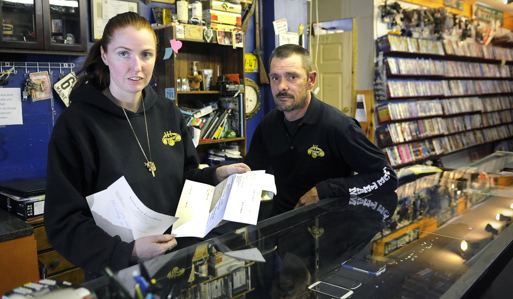 Amanda Bosse and Edwin Harris behind the counter of their Augusta pawn shop, A&E Trading, on Tuesday. The proprietors recently won a court judgment to have a silver bar, seized by Augusta Police on suspicion it was stolen, returned to them.