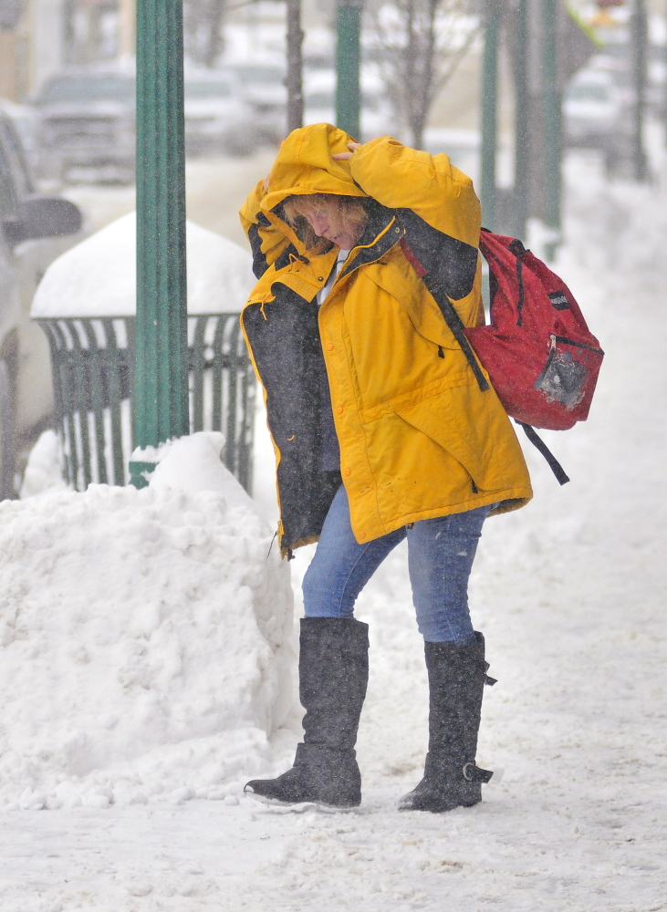 Teresa Merrill pulls up her hood against a cold wind while walking to her car Thursday as more snow blows across Water Street in downtown Gardiner.