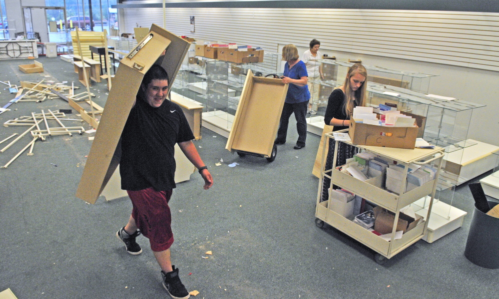 People clean out the former Beverly's Card and Gift on Tuesday at the Turnpike Mall in Augusta.