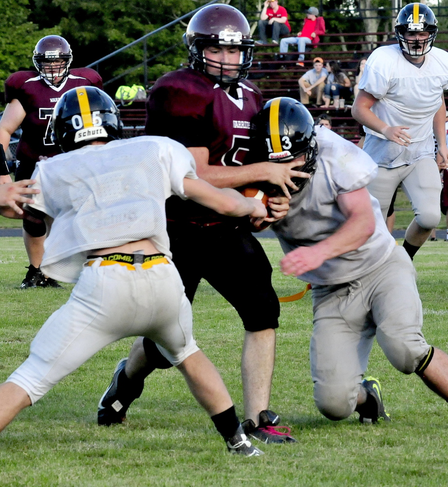 Staff photo by David Leaming   Nokomis quarterback Sam Whitmore gets squeezed between two Maranacook defenders during a scrimmage in Newport on Monday.