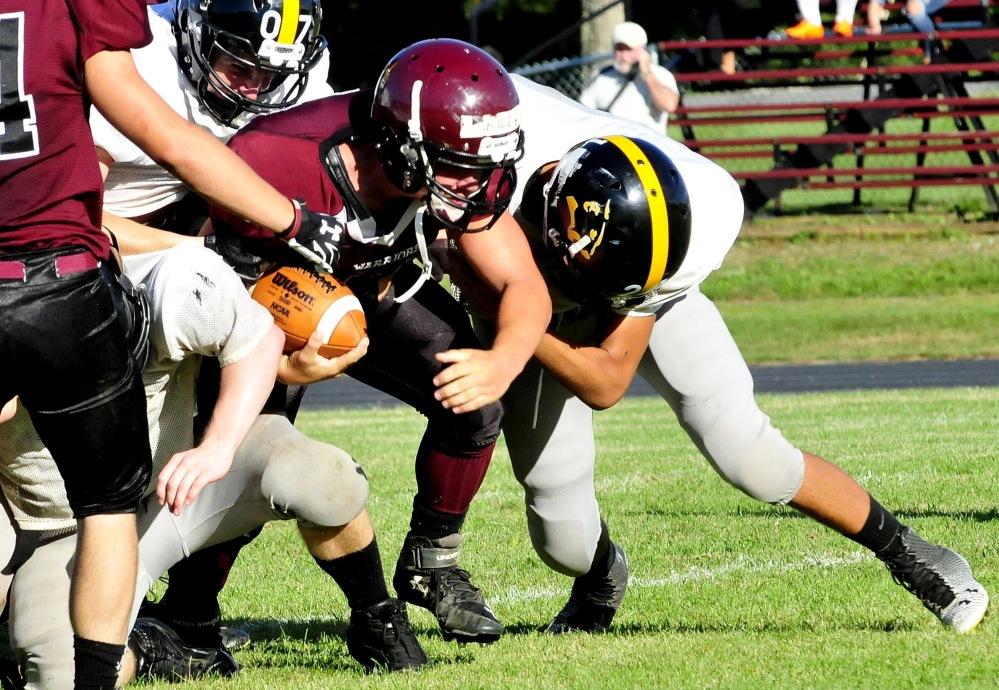 Staff photo by David Leaming   Nokomis' Cody Rice gets sacked by a Maranacook defender during a scrimmage in Newport on Monday.