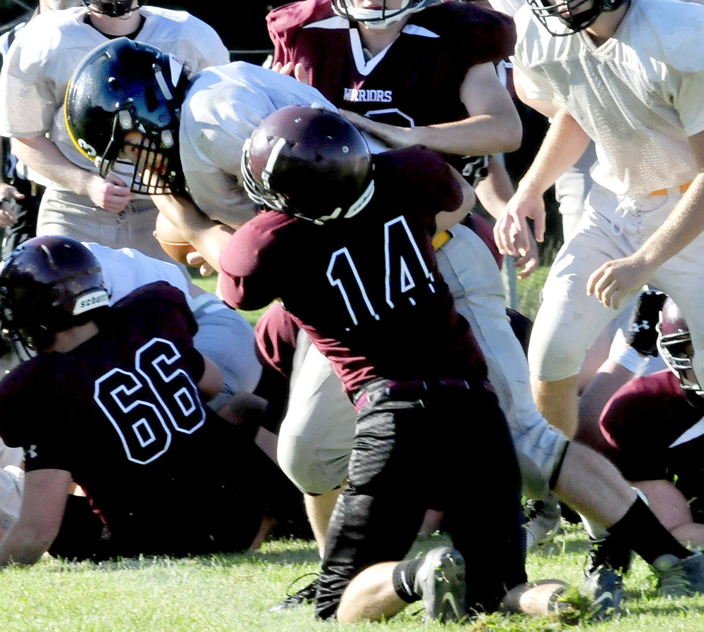 Staff photo by David Leaming   Maranacook quarterback Kyle Morand evades a tackle by Nokomis' Isaac Thibodeau during a scrimmage in Newport on Monday.