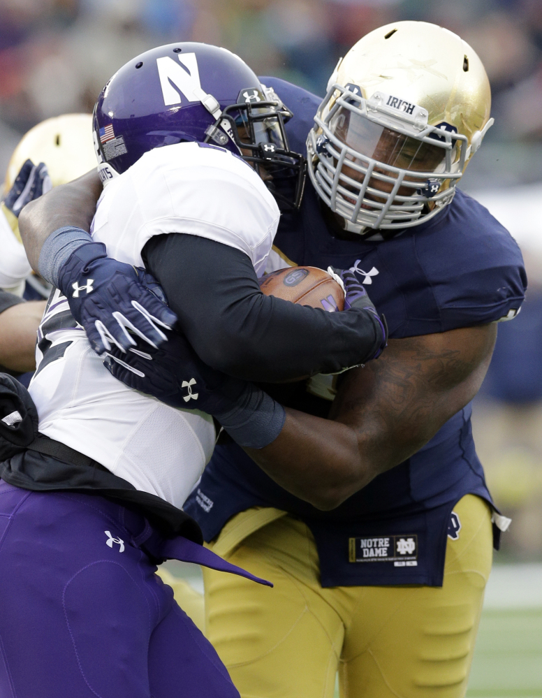 AP photo   In this Nov. 15, 2014, file photo, Notre Dame defensive lineman Jarron Jones, right, tackles Northwestern running back Treyvon Green during the first half of a game in South Bend, Ind. Jones, a returning starter who made 40 tackles last season, tore the medial collateral ligament in his right knee.