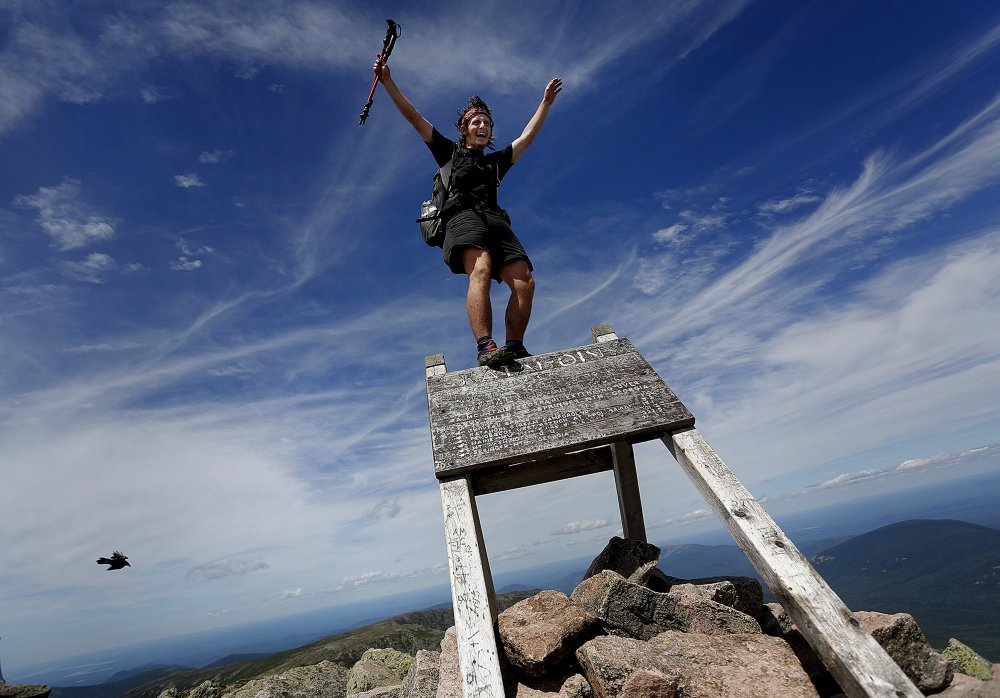 "In this July 19 file photo, Jesse Metzler, 19, of Newton, Ma., who goes by the trail name ""Sputnik,"" celebrates on the top of a sign marking the northern terminus of the Appalachian Trail at the summit of Mt. Katahdin in Baxter State Park. Baxter officials say thru-hikers are openly using drugs and drinking alcohol, camping where they aren't supposed to and trying to pass their pets off as service dogs. Jensen Bissell, director of the park, says the trail may need to end somewhere besides Katahdin if something doesn't change soon."