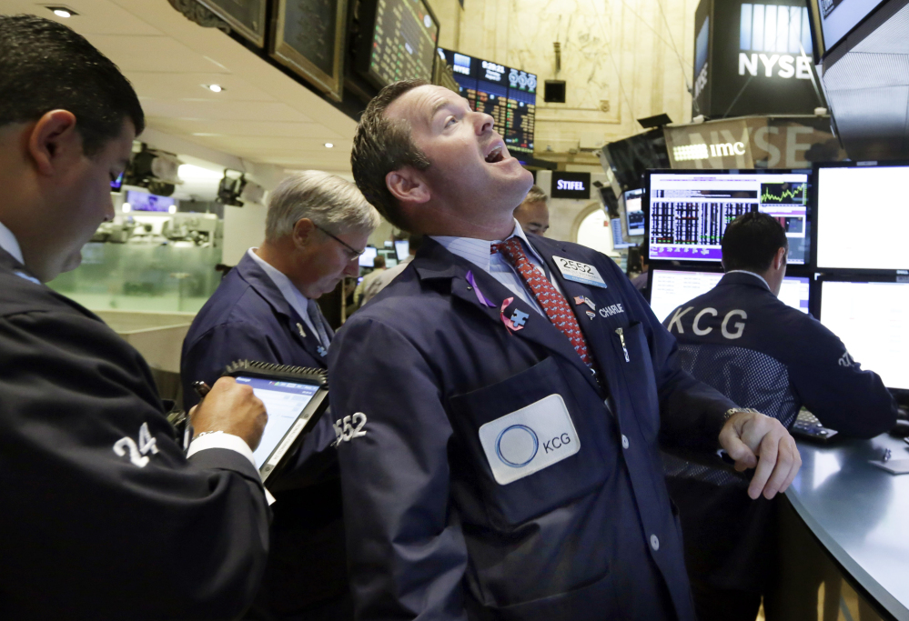 Specialist Charles Boeddinghaus, center, works on the floor of the New York Stock Exchange on Thursday. U.S. stocks opened higher after China's main stock index logged its biggest gain in eight weeks.