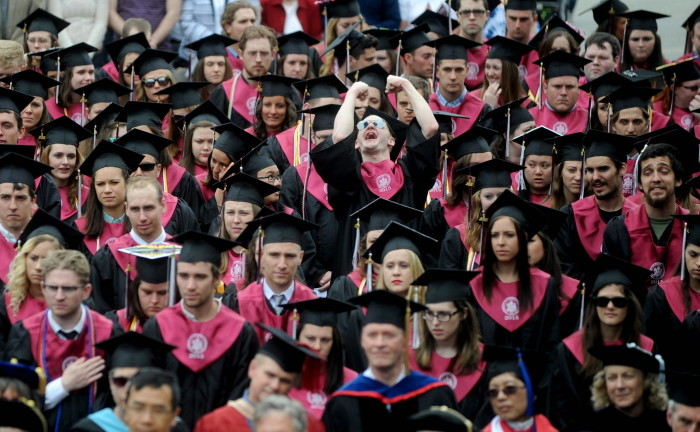 """Don Osthoff, right middle, stands up and celebrates as University of Maine's class of 2015 begins commencement ceremonies in Farmington in May. The school was ranked Maine's """"Best Bang for your Buck"""" Monday by Washington Monthly magazine and 14th nationally."""