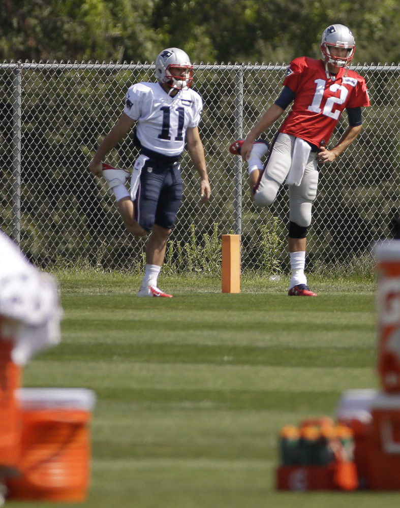 New England Patriots quarterback Tom Brady (12) and wide receiver Julian Edelman (11) stretch before practice begins at the team's facility Tuesdayin Foxborough, Mass.