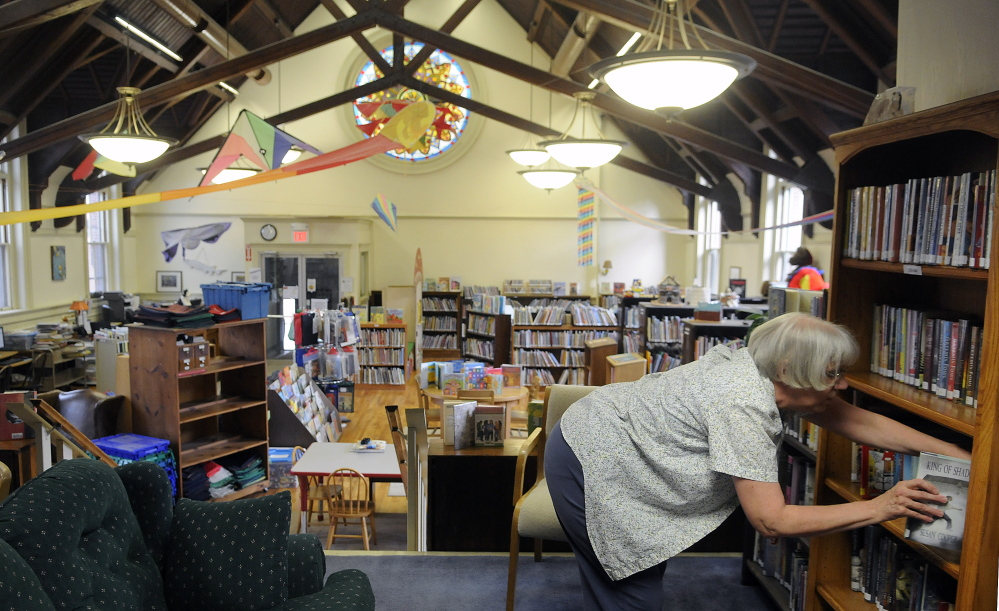 Gardiner Public Library teenage librarian Ginni Nichols sorts books in the children's reading room on Thursday.