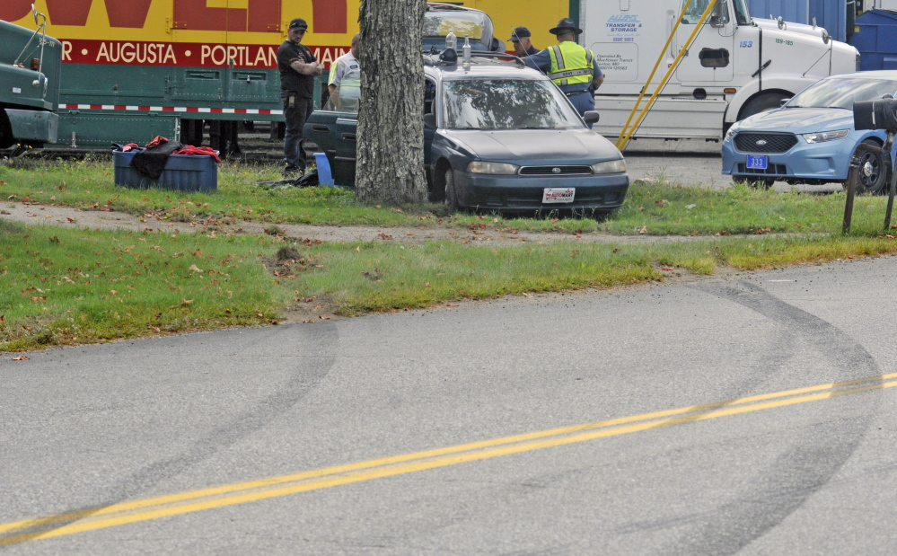 Skid marks lead the way to where tow truck drivers and State Police Troopers stand beside a crashed car on Thursday on Leighton Road in Augusta.