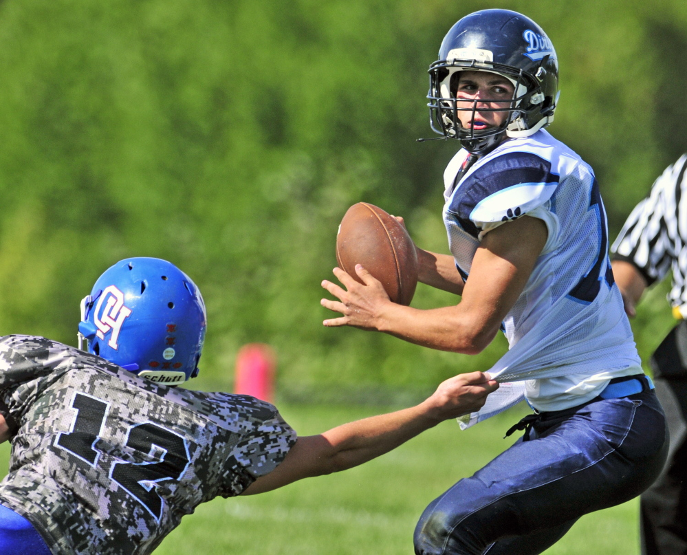 Oak Hill defensive end Matthew Strout, left, grabs the shirt but can't hang on to Dirigo quarterback Riley Robinson during third quarter Saturday in Wales.
